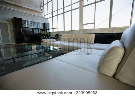 Glass table by empty white sofa at modern office