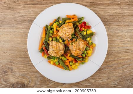 White Plate With Vegetable Mix And Meatballs On Wooden Table