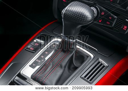 Automatic gear stick with red stich of a modern car. Car interior details. Dashboard with buttons