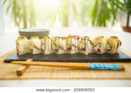 Sushi With Salmon, Avocado, Rice In Seaweed And Chopsticks On Wooden Table. Japanese, Asian Healthy