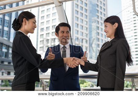 business man show thumb up and two business woman shaking hands for demonstrating their agreement to sign agreement or contract between their firms companies enterprises. success concept