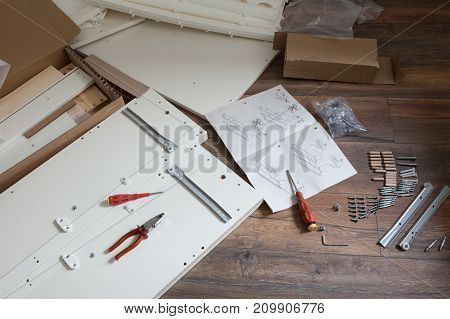 Furniture assembly parts and tools for self assembly furniture on the floor.