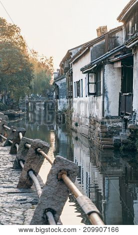 Suzhou, China - Nov 5, 2016: Peaceful narrow path of cobblestone at the historic Zhouzhuang Water Town. Path is along a water canal and has bamboo and stone railing.