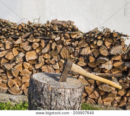 axe on the chopping block with chopped wood pile leveled on white wall