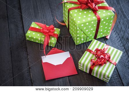 Gift boxes wrapped in green paper tied with red ribbon and bows and an opened red letter on a black wooden table.