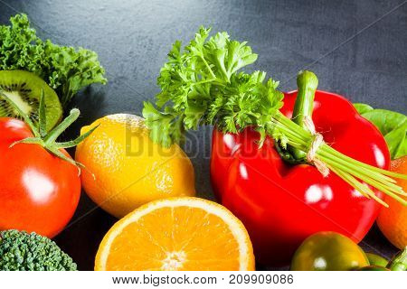Group of fruits and vegetables on black slate.