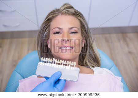 High angle view of dentist holding tooth whitening equipment by smiling patient at clinic