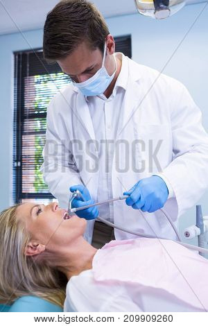Dentist cleaning woman teeth while standing against wall at dental clinic