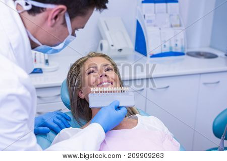 Doctor holding tooth whitening equipment by smiling patient at medical clinic