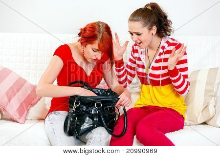 Indignant young girl sitting on sofa and looking on searching something in handbag girlfriend
