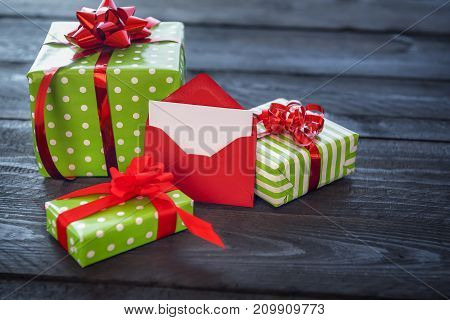 Colorful presents wrapped in paper and tied with red ribbon and bows with an opened red letter leaned against them on vintage background.