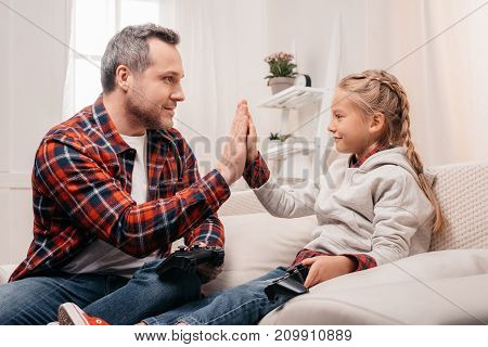 smiling father and daughter giving high five while playing with joysticks at home