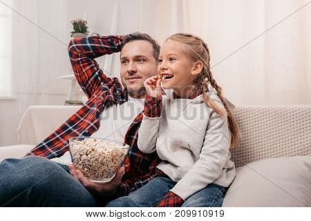 Father And Daughter Eating Popcorn