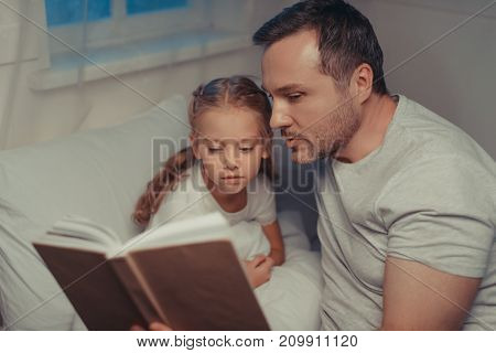 Family Reading Book At Bedtime