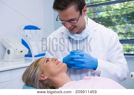 Smiling dentist looking at patient in medical clinic
