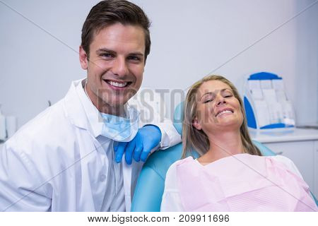 Portrait of smiling patient and dentist sitting on chair at dental clinic