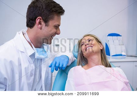 Smiling patient looking at dentist while sitting on chair at dental clinic