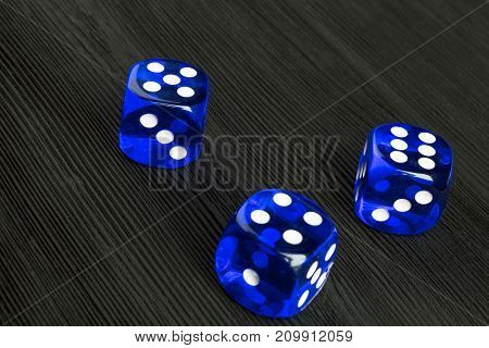 risk concept - playing dice at black wooden background. Playing a game with dice. Blue casino dice rolls. Rolling the dice concept for business risk chance good luck or gambling