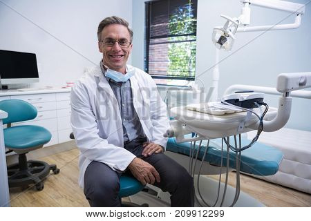 Portrait of smiling dentist sitting on chair at medical clinic
