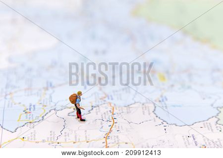 Miniature traveler with backpack standing on wold map for travel around the world. Travel Concept