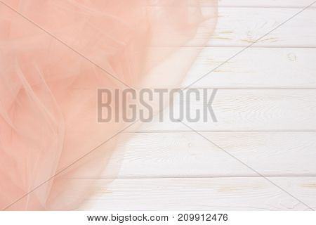 Beautiful layers of gentle pink background with tulle fabric on a wooden background
