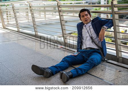 businessman wear blue suit sitting on the street He is saddened by the business failure. concept of business failure and unemployment problem