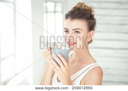 Pretty young woman holding a cup of coffee and smiling as she looks thoughtfully to the side in a bright airy room with copy space