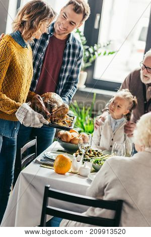 man and woman carrying turkey for thanksgiving dinner while excited family looking at it