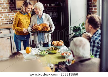 senior woman and her daughter carrying turkey for thanksgiving dinner with their large family