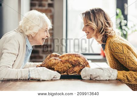 happy senior mother and daughter with delicious turkey on tray