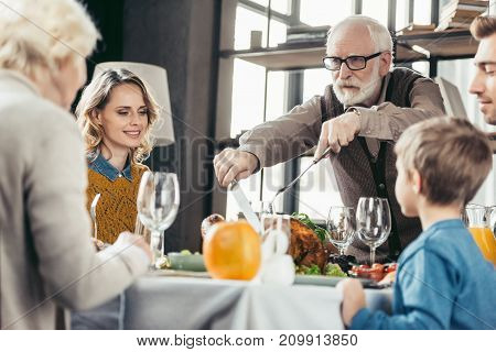 Grandfather Cutting Turkey For Family
