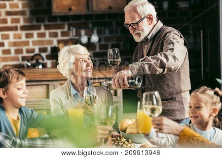 senior man pouring wine for woman while their family clinking glasses on holiday dinner