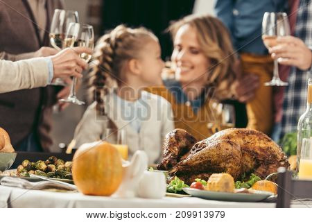 happy mother and daughter embracing at thanksgiving holiday table