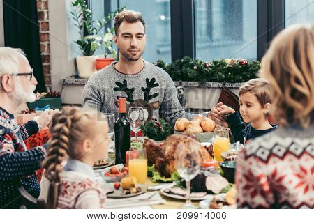 beautiful family praying at christmas table before dinner