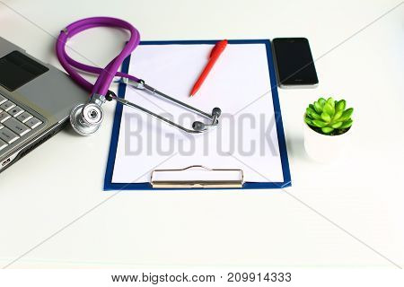 Doctor's workspace working table with patient's discharge blank paper form, medical prescription, stethoscope on desk.