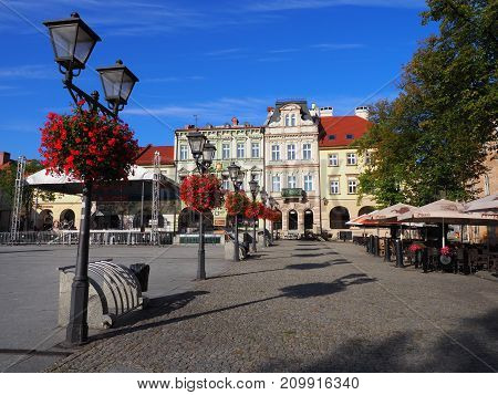 BIELSKO-BIALA POLAND EUROPE on AUGUST 2017: Main square in historical city center with colorful old buildings street lamps and red flowers clear blue sky in warm sunny summer morning day.