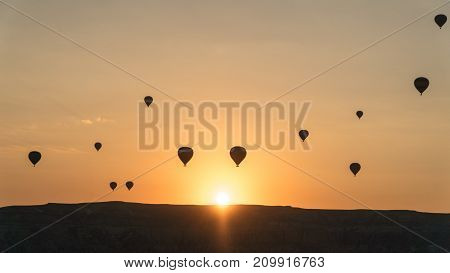 Cappadocia Turkey - August 2017: Silhouettes of hot air balloons flying above rocky landscape in Cappadocia Turkey
