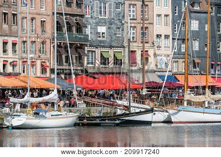 HONFLEUR, FRANCE - AUGUST 24, 2017: Harbor of historic city Honfleur with moord sailing ships. Many tourists enjoy the sunny weather and take a lunch at an outside terrace