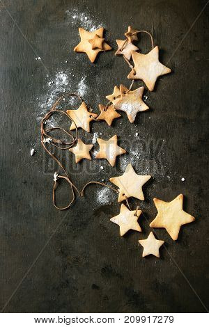 Garland of homemade shortbread star shape sugar cookies different size on thread with sugar powder over dark texture surface. Christmas treat background. Top view with space