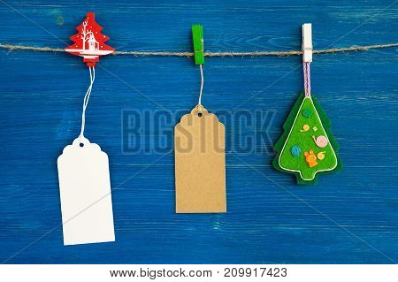 Brown And White Blank Paper Price Tags Or Labels Set And Christmas Decorations Hanging On A Rope On