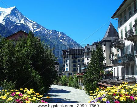 CHAMONIX MONT BLANC village with high alpine mountains range landscape in french ALPS with colorful flowers at Arve river in FRANCE with clear blue sky in 2016 warm sunny summer day EUROPE on July.