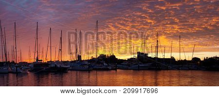 A vivid orange marina sunrise with water reflections and boats in silhouette. An absolutly stunning end to a most enjoyable nautical day. QueenslandAustralia.