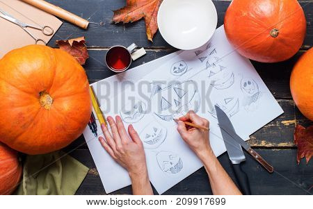 drawing sketch character with hands pumpkin knife bowl pencil object on black planks preparation to halloween holiday background top view