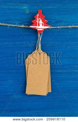Brown Blank Paper Price Tags Or Labels Set And Christmas Wooden Decoration Hanging On A Rope On The