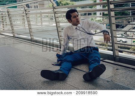 businessman unemployed from company sitting on the street A man desperate want to commit suicide. concept of business failure and unemployment problem