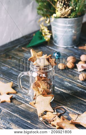 Homemade shortbread star shape sugar cookies different size in glass jar and as garland on old wooden table decorated by Christmas tree and gifts. Christmas mood theme. Toned image.