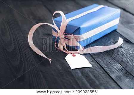 Classy blue gift tied with pink ribbon and bow with an empty label tied to it on an old wooden table.