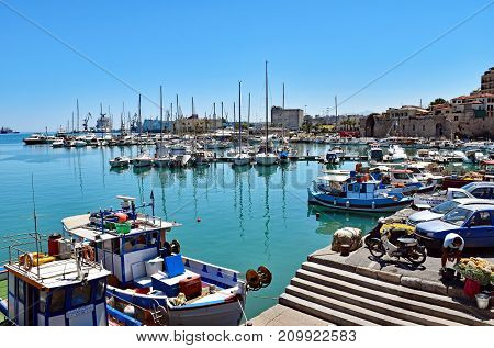 Heraklion, Greece - July 15, 2016: Small fishing boats and yachts are moored in the Old Venetian Harbor of Heraklion on the island of Crete, Greece.