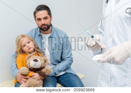 cropped shot of female doctor with syringe and blurred man with his daughter on background