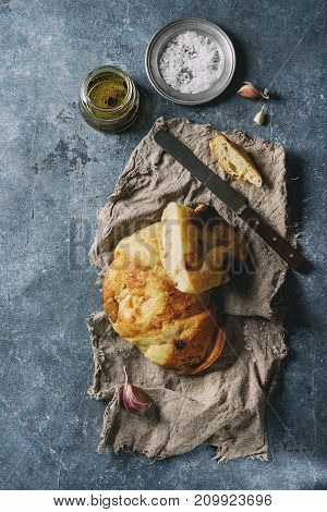Homemade white wheat garlic bread on sackcloth with salt, olive oil and balsamic vinegar on blue texture background. Top view with space. Toned image